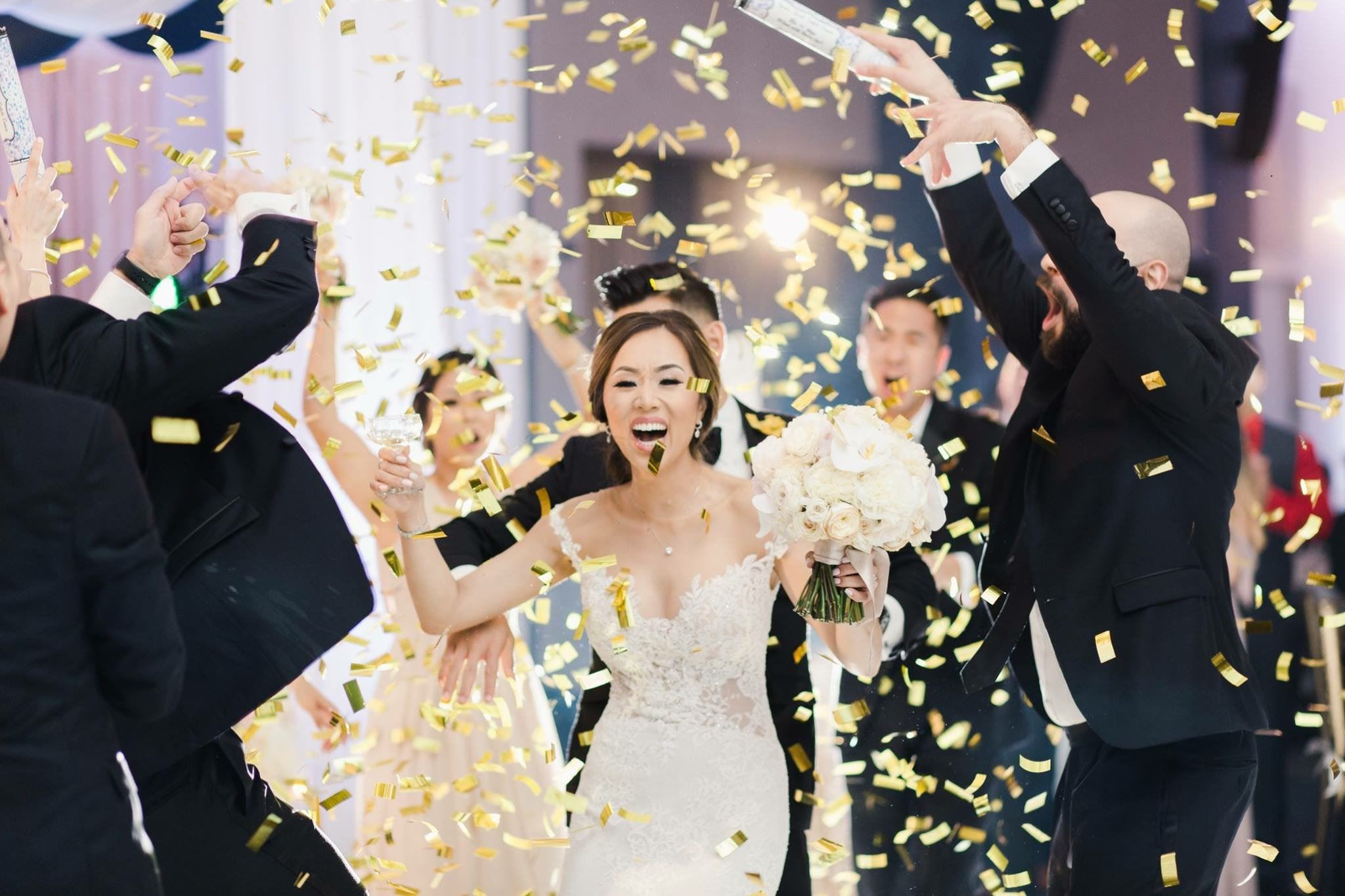 A bride is showered in gold confetti